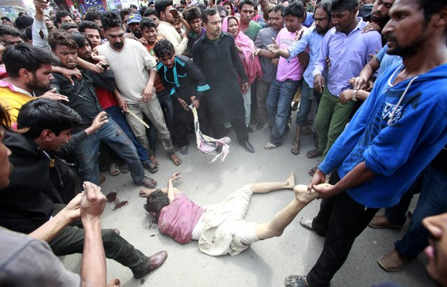Enraged Christians lynch a man they suspected of being involved in a suicide attack on a church in Lahore March 15, 2015. Bombs outside two churches in the Pakistani city of Lahore killed 14 people and wounded nearly 80 during Sunday services, and witnesses said quick action by a security guard prevented many more deaths. A Pakistani Taliban splinter group claimed responsibility. (Photo by Mohsin Raza/Reuters)