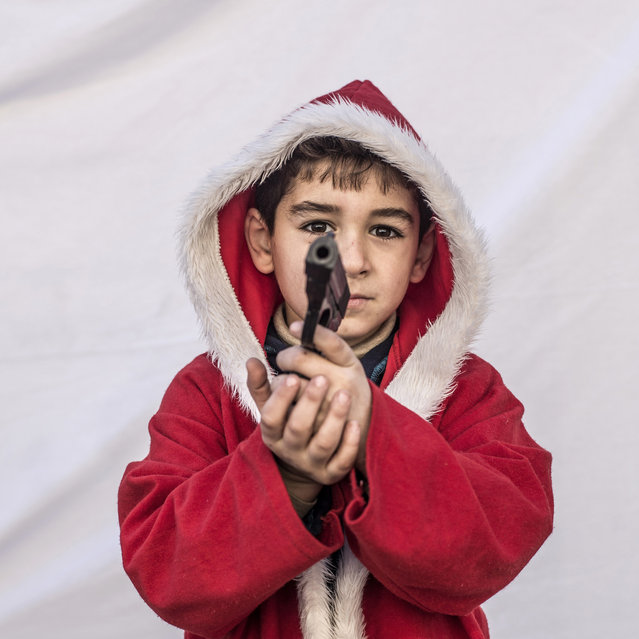 Kayaks, 7, poses for a picture holding toy gun in a camp where Christians displaced by Islamic State militants are living, in Irbil, Iraq, Friday, December 23, 2016. Iraq's Christians are marking the holiday in his camp for displaced people with a sense of worry and despair,  unable to return to their towns they were forced to flee two years ago by the Islamic State group's onslaught. (Photo by Manu Brabo/AP Photo)