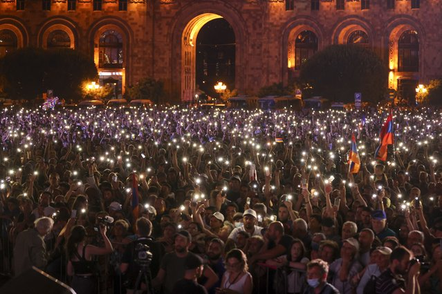 Supporters of Armenian acting Prime Minister Nikol Pashinyan hold up their phones during a rally in his support after winning snap parliamentary elections in Yerevan, Armenia, Monday, June 21, 2021. (Photo by Tigran Mehrabyan/PAN Photo via AP Photo)