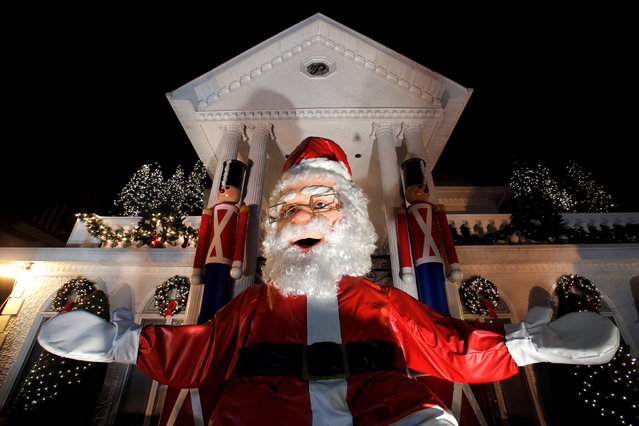 A large Santa Claus sits at the entrance of a decorated house at the Dyker Heights Christmas Lights in the Dyker Heights neighborhood of Brooklyn, New York City, U.S., December 23, 2016. (Photo by Andrew Kelly/Reuters)