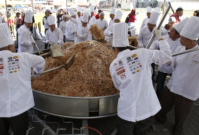 """Chinese residents in Costa Rica cook Cantonese fried rice during Chinese Lunar New Year celebrations in Chinatown in San Jose February 12, 2013. Some 52 chefs from various Chinese restaurants in Costa Rica cooked the """"world's largest Cantonese fried rice"""", which weighed 1,345kg (2,965 lbs), and served over 7,000 people, according to Isabel Yung, President of the Chinese Residents Association in San Jose. The event was attended by a judge from the Guinness Book of World Records who certified the effort. (Photo by Juan Carlos/Reuters)"""