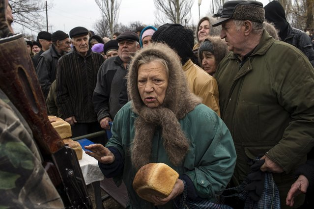 People queue for free bread distributed by pro-Russian rebels in the village of Chornukhyne near the town of Debaltseve, north-east from Donetsk, March 12, 2015. (Photo by Marko Djurica/Reuters)