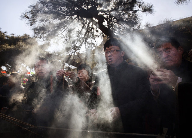 Chinese worshippers light incense and pray at the Yongchegong Lama Temple on February 8, 2016 in Beijing, China. The Chinese Lunar New Year also known as the Spring Festival, which is based on the Lunisolar Chinese calendar, is celebrated from the first day of the first month of the lunar year and ends with Lantern Festival on the fifteenth day. (Photo by Kevin Frayer/Getty Images)