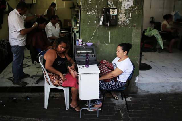 A woman gets her pedicure done by a street nail technician at a street in Rio de Janeiro, Brazil, January 6, 2017. (Photo by Nacho Doce/Reuters)