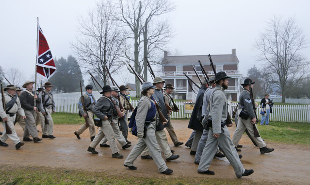 Confederate troops march in front of the McLean House as they prepare for battle during a re-enactment of the Battle of Appomattox Courthouse as part of  commemoration of the 150th anniversary of the surrender of the Army of Northern Virginia at Appomattox Court House in Appomattox, Va., Thursday, April 9, 2015. (Photo by Steve Helber/AP Photo)