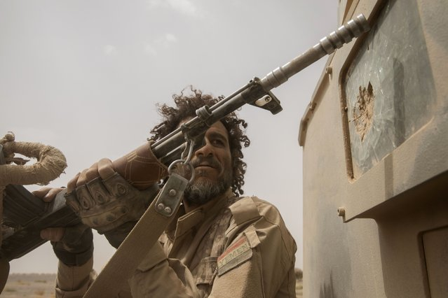 A Yemeni fighter backed by the Saudi-led coalition looks at damage to the back of an armored vehicle as they leave the front lines near Marib, Yemen, Saturday, June 19, 2021. (Photo by Nariman El-Mofty/AP Photo)
