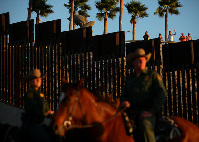 People in Mexico wave at U.S. Border Patrol agents on horseback patrolling the U.S.-Mexico border fence near San Diego, California, U.S., November 10, 2016. (Photo by Mike Blake/Reuters)