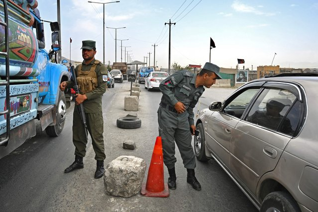 Afghan policemen stand guard at a checkpoint along the road in Kabul on August 14, 2021. (Photo by Wakil Kohsar/AFP Photo)