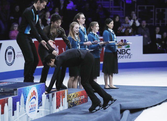 Nathan Chen is helped as he approaches the winner's podium after winning the men's free skate during the U.S. Figure Skating Championships, Sunday, January 27, 2019, in Detroit. (Photo by Carlos Osorio/AP Photo)