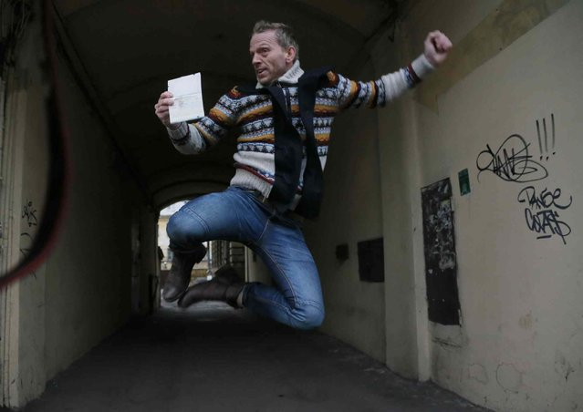 Greenpeace International activist Mannes Ubels of Netherlands jumps holding his passport as he celebrates getting permission to leave Russia, near the Federal Migration Service in St.Petersburg, Russia, Thursday, December 26, 2013. Russian investigators have dropped charges against all of the 30 crew of a Greenpeace ship, who were accused of hooliganism following a protest outside a Russian oil rig in the Arctic. (Photo by Dmitry Lovetsky/AP Photo)