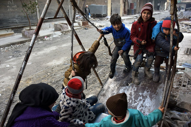 Syrian children play in a damaged street in Aleppo' s Tareeq al- Bab neighbourhood on January 18, 2017, a month after government forces retook the northern Syrian city from rebel fighters. (Photo by George Ourfalian/AFP Photo)
