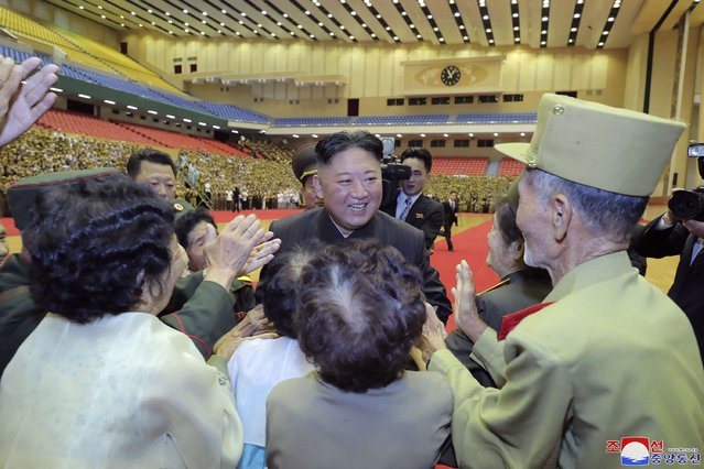 """In this photo provided by the North Korean government, North Korean leader Kim Jong Un, center, is welcomed by participants of a veteran conference in Pyongyang, North Korea, Thursday, July 29, 2021. North Korea said Friday, July 30, 2021 that Kim called for stronger capability to cope with any foreign provocation as he met with military officers ahead of annual drills next month between South Korea and the United States that Pyongyang views as an invasion rehearsal. Independent journalists were not given access to cover the event depicted in this image distributed by the North Korean government. The content of this image is as provided and cannot be independently verified. Korean language watermark on image as provided by source reads: """"KCNA"""" which is the abbreviation for Korean Central News Agency. (Photo by Korean Central News Agency/Korea News Service via AP Photo)"""