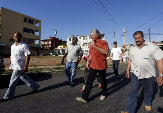 Cuba's First Vice-President Miguel Diaz Canel (red shirt), walks with his wife Lis Cuesta (partially obscured) and bodyguards after casting his vote at a polling station in Havana April 19, 2015. (Photo by Reuters/Stringer)