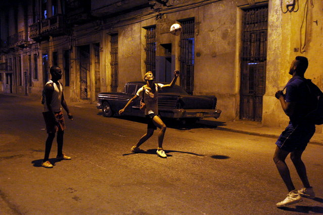 Street seller David Garcia plays with a soccer ball with his friends Luis Enrique who is attending military service, and Yaciel Concepcion, who is a physics teacher, in downtown Havana, March 5, 2015. (Photo by Alexandre Meneghini/Reuters)