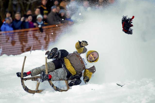 """Men soar through the air on a wooden sledge during a traditional Bavarian horn sledge race, known as """"Schnablerrennen"""", in Gaissach near Bad Toelz, Germany, January 22, 2017. (Photo by Michael Dalder/Reuters)"""