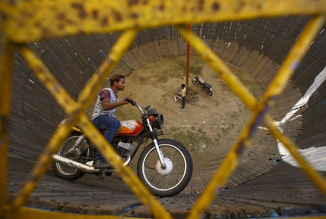 "A stuntman rides a motorcycle inside the ""Well of Death"" attraction during a fair in Bhaktapur April 20, 2015. (Photo by Navesh Chitrakar/Reuters)"