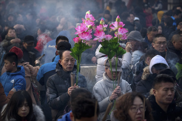 People hold floral bouquets and sticks of incense as they pray at the Lama Temple in Beijing, Tuesday, February 5, 2019. Chinese people are celebrating the first day of the Lunar New Year on Tuesday, the Year of the Pig on the Chinese zodiac. (Photo by Mark Schiefelbein/AP Photo)