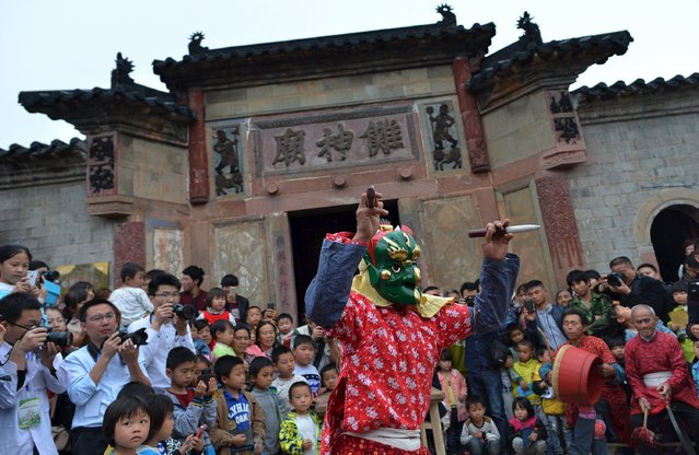 "People watch a man wearing a mask perform a ritual dance named ""Nuo"" at Shiyou village of Nanfeng county, Jiangxi province, April 18, 2015. ""Nuo"" is an ancient festival believed to exorcise evil spirits causing plague. (Photo by Reuters/Stringer)"