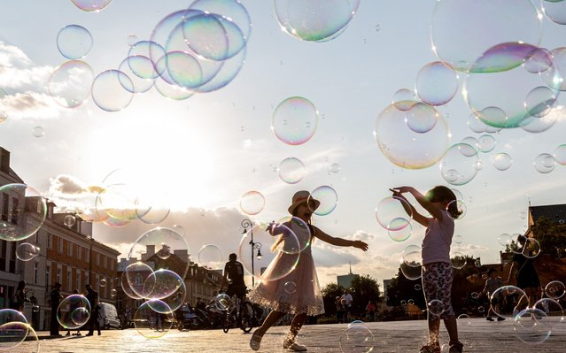 Children are seen playing with soap bubbles as Poles enjoy first hot day after particularly cold spring in Krakowskie Przedmiescie by the Royal Castle in an Old Town of Warsaw, Poland on June 25, 2020. (Photo by Dominika Zarzycka/NurPhoto via Getty Images)