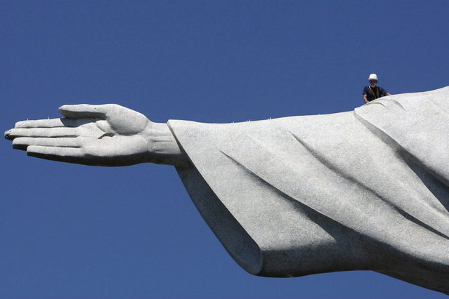 A worker inspects the Christ the Redeemer statue which was damaged during lightning storms in Rio de Janeiro January 21, 2014. Lightning strikes damaged the iconic figure's head and its right hand. The statue was hit on January 17 when a powerful electric storm swept through the city emitting more than 40,000 lightning strikes throughout the state of Rio de Janeiro. (Photo by Severino Silva/Reuters/Agência o Dia)