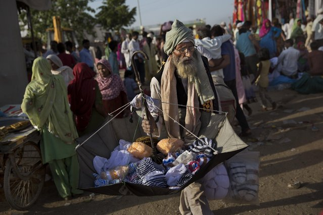 An Indian street vendor sells clothes in a makeshift camp for Sufi Muslim devotees during the Urs Festival in Ajmer, in the western Indian state of Rajasthan, India, Saturday, April 25, 2015. Thousands of pilgrims from different parts of India have arrived in the city for the yearly Urs that marks the death anniversary of the Sufi saint Khwaja Moinuddin Chishti. (Photo by Bernat Armangue/AP Photo)