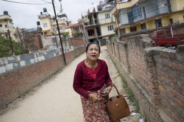 An elderly Nepalese woman reacts during an aftershock, in Kathmandu, Nepal, Sunday, April 26, 2015. (Photo by Bernat Armangue/AP Photo)