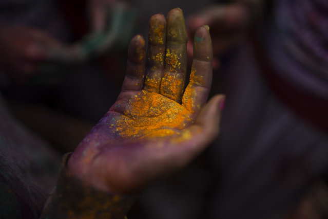A reveler holds her hand full of powder during a Holi Festival in Madrid, Spain, Sunday, April 26, 2015. (Photo by Andres Kudacki/AP Photo)
