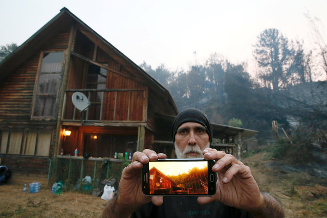 Cristian Gutierrez, a resident of Florida town, shows a picture he took of his house during a wildfire in the country's central-south regions, in Florida, Chile January 28, 2017. (Photo by Rodrigo Garrido/Reuters)