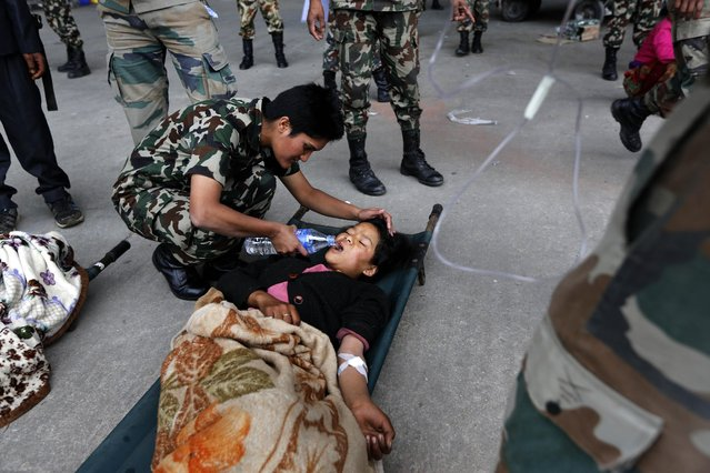 An Indian Army doctor helps an injured woman drink water after she was evacuated from higher reaches of mountains by Nepalese army, in Kathmandu, Nepal, Wednesday, April 29, 2015. The first aid shipments reached a hilly district near the epicenter of Nepal's earthquake, a U.N. food agency official said, and distribution of food and medicine would start Wednesday, five days after the quake struck. (Photo by Manish Swarup/AP Photo)