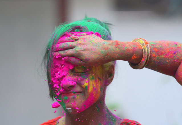 A girl is covered in powder by her friends in Agartala, the capital of the north-eastern state of Tripura, India on March 20, 2019. (Photo by Abhisek Saha/Barcroft Images)