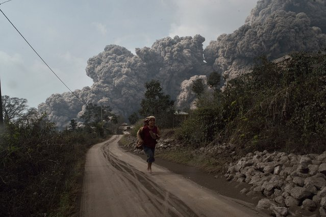 A resident runs away to escape from hot volcanic ash clouds engulfing villages in Karo district during the eruption of Mount Sinabung volcano located in Indonesia's Sumatra island on February 1, 2014. (Photo by Sutanta Aditya/AFP Photo)