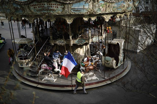 A man carrying a French national flag walks past a carousel near Sacre Coeur in Paris, Saturday, March 23, 2019. The French government vowed to strengthen security as yellow vest protesters stage a 19th round of demonstrations, in an effort to avoid a repeat of last week's riots in Paris. (Photo by Kamil Zihnioglu/AP Photo)