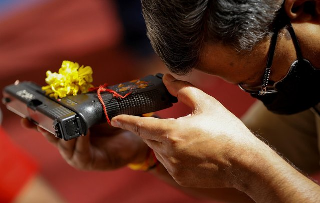 A police officer offers a prayer to his weapon as part of a ritual at their headquarters on the occasion of Dussehra, or Vijaya Dashami, festival in Ahmedabad, India, October 15, 2021. (Photo by Amit Dave/Reuters)