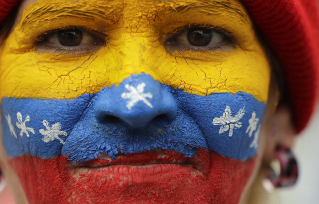 """Her face painted in the colors of the national flag, a supporter of opposition leader Juan Guaido, Venezuela's self-proclaimed interim president, waits for his arrival in Los Teques, Miranda State, Venezuela, Saturday, March 30, 2019. Guaido addressed the crowd while Maduro loyalists gathered for what was billed as an """"anti-imperialist"""" rally in the capital. Such dueling demonstrations have become a pattern in past weeks as Venezuela's opposing factions vie for power in a country enduring economic turmoil and a humanitarian crisis. (Photo by Natacha Pisarenko/AP Photo)"""