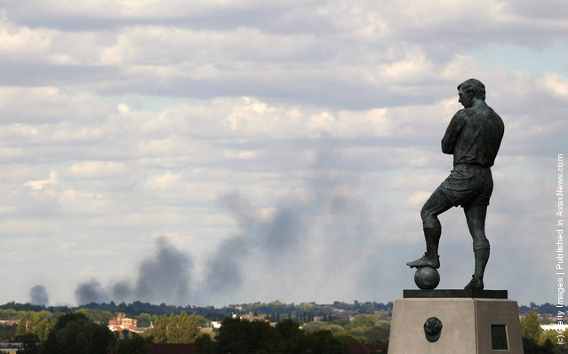 Smoke is seen over north London from a view behind the Bobby Moore statue outside Wembley Stadium as the England v Netherlands game is called off at Wembley Stadium following a night of rioting on August 9, 2011 in London, England