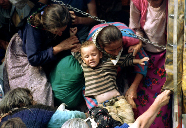 Bosnian Muslim women, refugees from Srebrenica, pull a child onto a truck before being transported from the eastern Bosnian village of Potocari, July 1995. Radovan Karadzic is the highest-ranking person to face a reckoning before the U.N. tribunal in The Hague over a war two decades ago in which 100,000 people were killed as rival armies carved Bosnia up along ethnic lines that largely survive today. (Photo by Reuters)