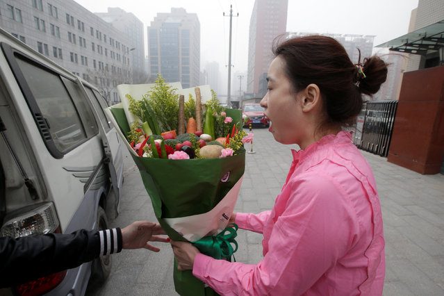 A woman reacts as she receives a bouquet made of vegetables and flowers, priced at 238RMB, from a delivery staff of a florist outside an office building on Valentine's Day in Beijing, China, February 14, 2017. (Photo by Jason Lee/Reuters)