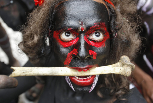 A man dressed as a demon performs with a bone during a religious procession at the Mahashivratri festival in the northern Indian city of Allahabad February 27, 2014. (Photo by Jitendra Prakash/Reuters)
