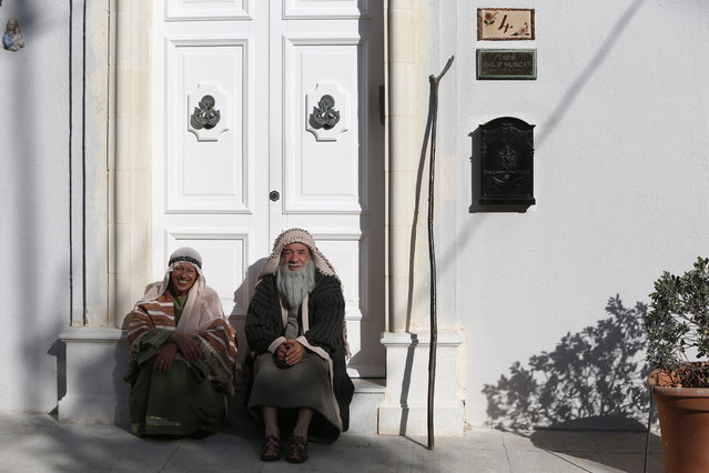 Participants sit on a doorstep while waiting for the start of a Good Friday procession in the village of Zebbug, outside Valletta, Malta, March 25, 2016. (Photo by Darrin Zammit Lupi/Reuters)