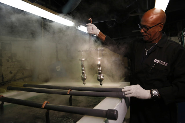 Cecil Bowen works on Oscar statuettes that have already been nickel plated at Epner Technology in the Brooklyn borough of New York, Tuesday,  January 17, 2017. (Photo by Seth Wenig/AP Photo)