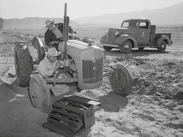 Driver Benji Iguchi looks on as mechanic Henry Hanawa repairs a tractor engine at the Manzanar War Relocation Center in California, in this 1943 handout photo. (Photo by Courtesy Ansel Adams/Library of Congress, Prints and Photographs Division/Reuters)