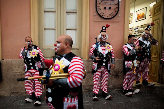 "Members of the ""Afilarmonica Nifu-Nifa"" carnival group wait outside their headquarters before they take part in the opening parade of the Carnival in Santa Cruz de Tenerife on the Canary island of Tenerife, Spain, February 28. ""Afilarmonica Nifu-Nifa"" received its name in 1961 and is the oldest carnival group of the city. (Photo by Blazquez Dominguez/Getty Images)"