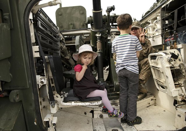 A U.S. serviceman speaks to a boy inside an armored combat vehicle in Ploiesti, Romania, Wednesday, May 13, 2015. (Photo by Vadim Ghirda/AP Photo)