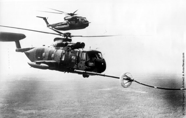 Two battle modified US Sikorsky S-61 helicopters being refuelled in mid-air over Vietnam