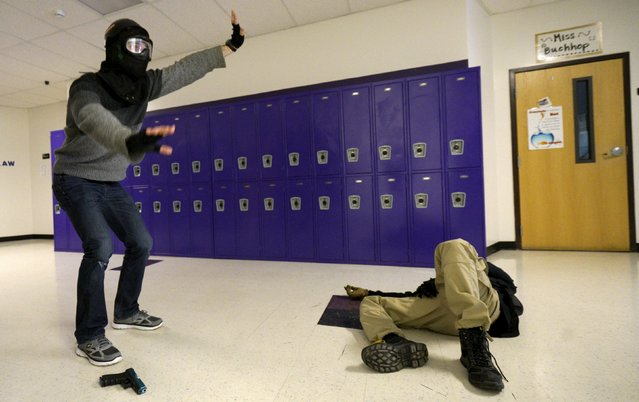 A student (L) responds to commands from a simulated law enforcement training, with a mock victim on the floor in a middle school, during an Active Shooter Response course offered by TAC ONE Consulting in Denver April 2, 2016. (Photo by Rick Wilking/Reuters)