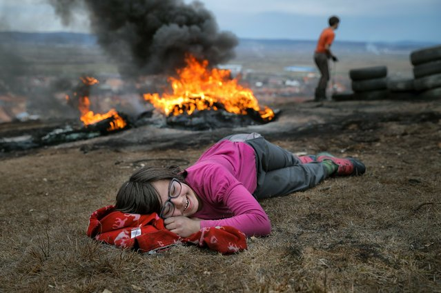 In this photo taken on Sunday, March 10, 2019, a little girl laughs during a ritual marking the upcoming Clean Monday, the beginning of the Great Lent, 40 days ahead of Orthodox Easter, on the hills surrounding the village of Poplaca, in central Romania's Transylvania region. Romanian villagers burn piles of used tires then spin them in the Transylvanian hills in a ritual they believe will ward off evil spirits as they begin a period of 40 days of abstention, when Orthodox Christians cut out meat, fish, eggs, and dairy. (Photo by Vadim Ghirda/AP Photo)