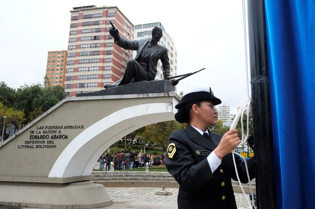 """A Bolivian navy officer hoists a flag during a ceremony that marks """"The month of the Sea"""" at the Eduardo Avaroa square in La Paz, Bolivia March 1, 2017. Bolivia lost its access to the sea to Chile during the 1879-1883 War of the Pacific. (Photo by David Mercado/Reuters)"""