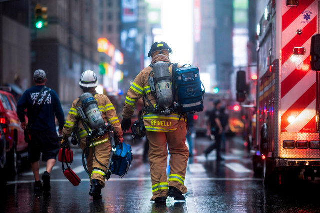 """Firemen are seen after a helicopter crash-landed on top of a building in midtown Manhattan in New York on June 10, 2019. Speaking at the scene New York Governor Andrew Cuomo told reporters there had been """"casualties"""" on board the helicopter, but that no one in the building had been hurt. (Photo by Johannes Eisele/AFP Photo)"""