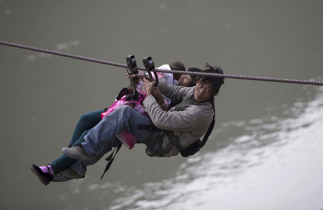 A man, his wife and their child use a zip-line to cross the Nujiang River in Lazimi village of Nujiang Lisu Autonomous Prefecture March 22, 2014. Residents have been using the zip-line for years to cross the river as there is no bridge nearby, local media reported. (Photo by Wong Campion/Reuters)