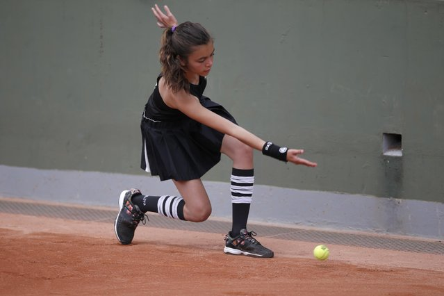 A ball girl passes the balls as Switzerland's Stefanie Voegele plays in the first round match of the French Open tennis tournament against Vitalia Diatchenko of Russia at the Roland Garros stadium, in Paris, France, Monday, May 25, 2015. (Photo by Francois Mori/AP Photo)
